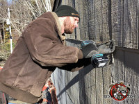 Technician on a platform lift with an electric screwdriver sealing bats out of a house in Signal Mountain Tennessee