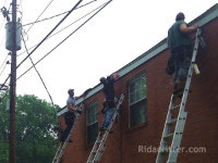 Three men on ladders sealing bats out of a building in Leeds, Alabama