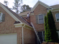 Man on a roof bat-proofing a house in Thomaston, Georgia