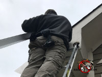 Man on a latter wearing a coat in the winter sealing bats out of the attic of a house in Woodbury Georgia