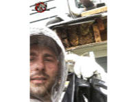 Male technician wearing a protective bee suit standing in from of an exposed bee hive in the soffit of a house in Chattanooga