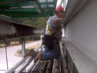 Man installing bird control netting at an industrial plant in Carrollton, Georgia