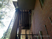 Bird control men on ladders installing bird repellent spikes in Homewood, Alabama