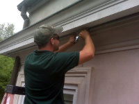 Man installing screening to keep carpenter bees out of a roof