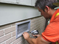 Technician installing an animal-proof crawl space vent in Fortson, Georgia