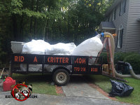Big bags of contaminated insulation pild onto a trailer after being removed from a Macon home