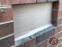 Homeowner unsuccessfully attempted to use cardboard to replace a missing foundation vent cover to keep mice out of a house in Pinehurst Georgia.