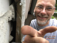 Smiling technician pointing out a gap between the foundation and the exterior trim that mice used to get into the house