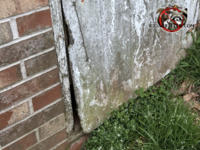 A rotten old wooden crawl space door is warped at the lower corner and needs to be replaced to keep mice out of a Forsyth Georgia home.
