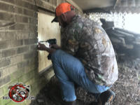 Man crouching under the deck of a house in Birmingham Alabama using a cordless screwdriver to attach a plywood panel to the foundation to seal mice out of the house