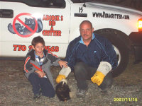 Skunk control expert David Cox and his son with a captured skunk
