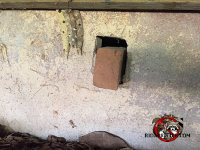 Homeowner attempted to seal rats out of the house by sticking a brick loosely into the hole in the foundation that the rats were using to get inside