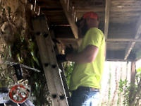 Man on a ladder under the deck of a house in Birmingham Alabama sealing Norway rats out of the foundation of the house