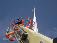 A squirrel-removal technician on a man lift in front of a church steeple