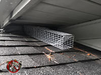 Squirrel trap on the roof of a house in Chattanooga with one end against a gap between the soffit panel and the shingles at a roof junction