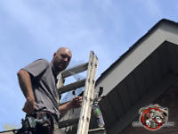 Bald man on a ladder sealing the roof of a house in Anniston Alabama to keep squirrels from getting into the attic