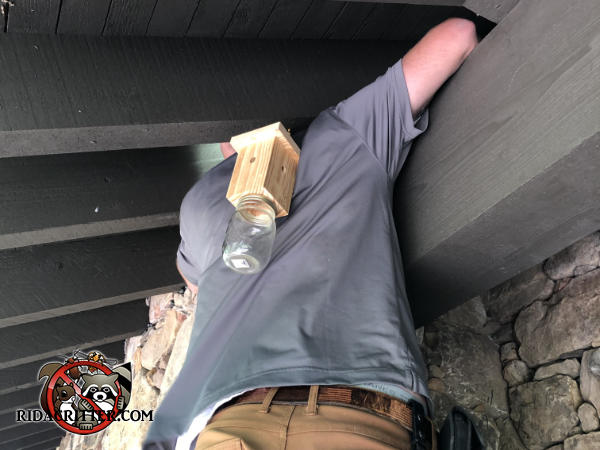 Man with his head and arms in the rafters over the porch of a stone house in Johns Creek Georgia sealing bats out of the house.