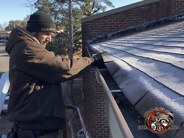 Man on a platform lift sealing bats out of the roof of an apartment house in Chattanooga Tennessee