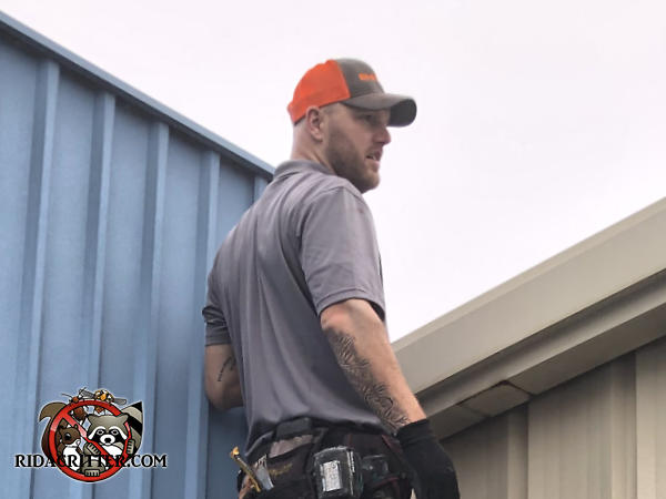 Man inspecting the roof of a commercial building in Chattanooga to determine how bats were getting into the building