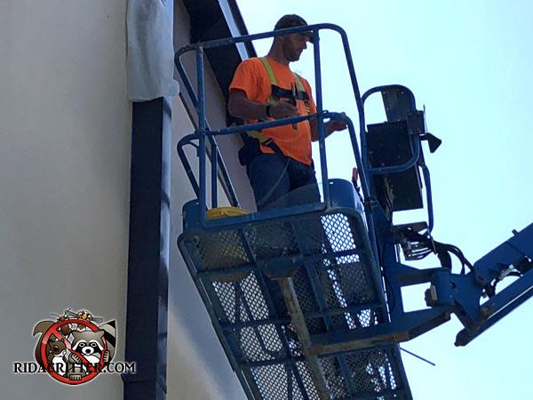 Man on a platform lift sealing bats out of a warehouse in downtown Atlanta