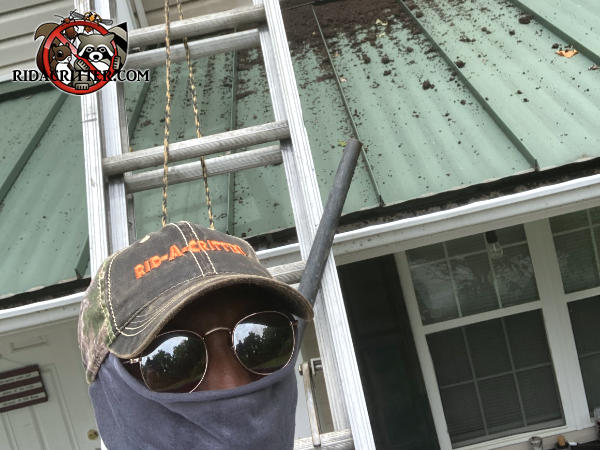 Man in a mask and sunglasses standing in front of a house in Concord Georgia with bat guano all over the metal roof and a ladder against the house