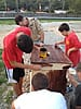 Boy Scouts and adult leader applying stain to a wooden flag storage box