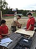 Scouts and adult leader assembling a flag storage box