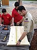 Scoutmaster measuring wood for a flag storage box