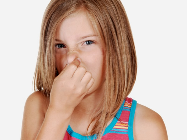 Little girl with disgusted expression holding her nose