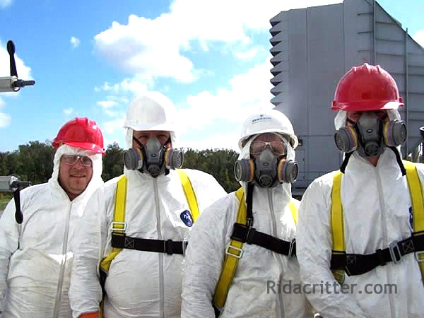 Bird control experts in white, protective bird-removal gear, hardhats, and respirators