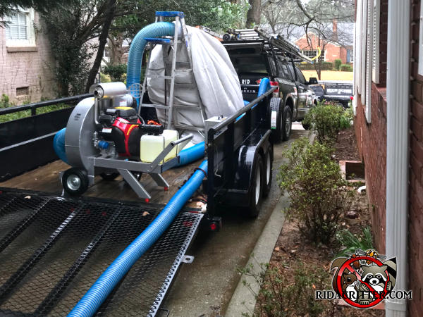 Rear of a pickup truck with a trailer containing a huge vacuum cleaner and filter bag full of contaminated insulation removed from the attic of a house in Chattanooga