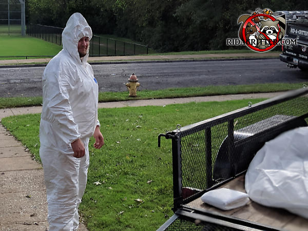 Man in a Tyvek suit standing next to a trailer holding a filter bag used to collect contaminated insulation from the attic of a house in Chattanooga