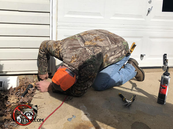 Man on his hands and knees sealing mice out of the foundation of a house in Jackson Georgia
