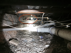 A rat exterminator in a crawl space in Birmingham, Alabama, barely visible among the pipes and debris