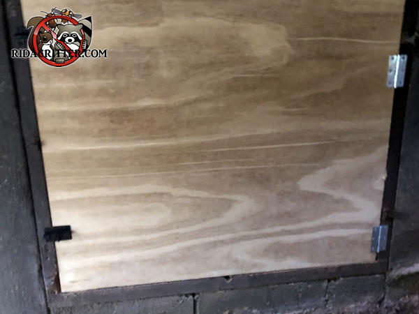 Tight fitting plywood crawl space door that was installed to keep Norway rats out of the crawl space of a house in Marietta Georgia.