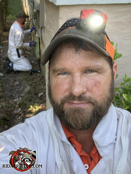 One man taking a selfie with another in the background sealing rats out of a house in Atlanta