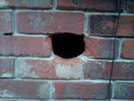 A rat hole in an exterior brick wall in Norcross, Georgia