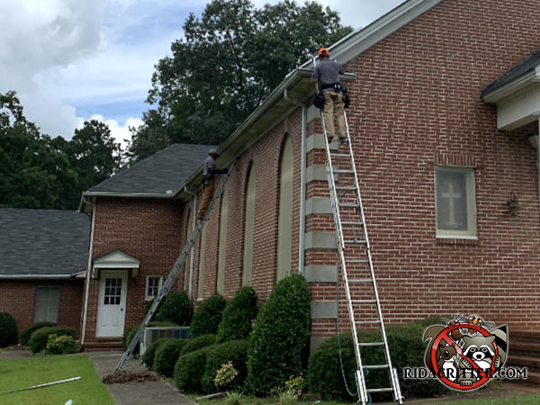 Two men on ladders sealing the edges of the roof to keep rats out of a church in Meansville Georgia