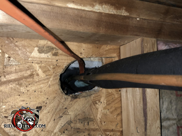 Inside view of a gap around pipes and wires that rats used to get into a house in Dallas Georgia