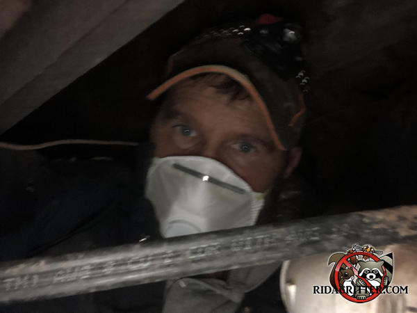 Selfie of a man wearing a protective mask and a hat while working in a crawl space sealing rats out of a house in Atlanta