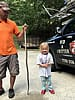 Snake removal technician holding a king snake vertically next to a toddler girl in Carrollton Georgia. The snake is longer than the girl is tall.