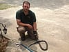 Snake removal worker with snake he removed from house in Hartwell, GA