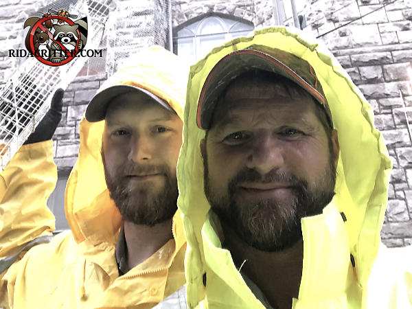 Two bearded male animal control technicians wearing rain gear with one holding a squirrel trap in front of a big church in Midtown Atlanta