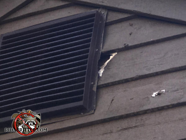 Squirrel hole in the wooden siding next to a gable vent at a house in Stone Mountain, Georgia