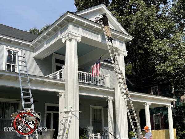 Man on a tall ladder replacing a squirrel damaged gable vent as part of an Albany Georgia squirrel removal and damage repair job.