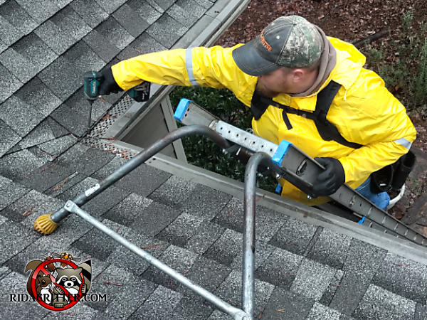 Man on a ladder with a cordless electric drill fastening the rain gutter cover to the roof to keep squirrels out of the attic of a house in Stone Mountain Georgia