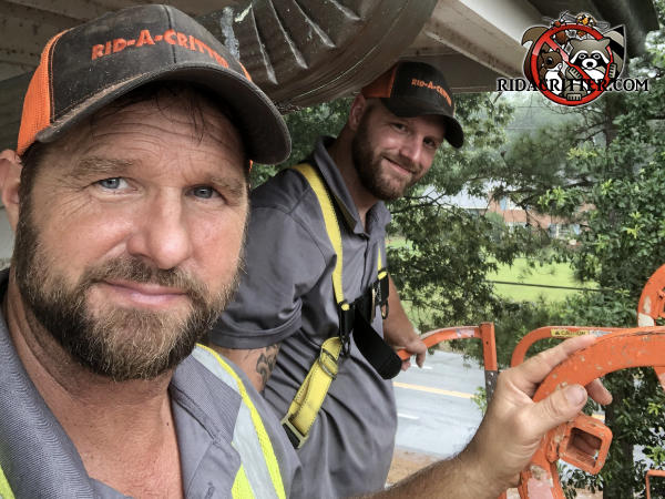 Two smiling men working aloft on a platform lift performing a squirrel removal and squirrel proofing job at a condominium building in Atlanta.